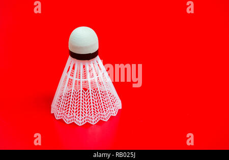 Shuttlecock in the lower right corner, on red background. copy space - Stock Photo