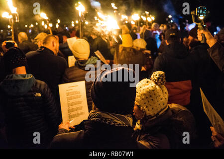 Herefordshire, UK. 5th Jan 2018.  A couple read the words to 'Wassail, Wassail, All Over The Town' a traditional Gloucestershire Wassail song, as members of the Silurian Morris and hundreds of members of the public who have walked from  Westons Cider Mill form a circle in the nearest orchard with fire torches to take part in the annual tradition of Wassailing on January 5, 2019 in Much Marcle, Herefordshire, England Credit: Jim Wood/Alamy Live News - Stock Photo