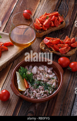 Baby calamari in olive oil with bruschettas and wine. - Stock Photo