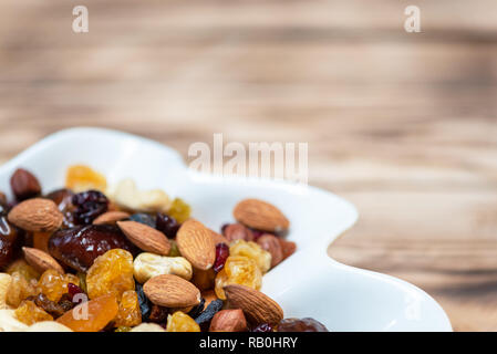 Dried fruits in white plate on wooden table. Mix of different varieties of nuts and berries, vitamins. With copy space for text - Stock Photo