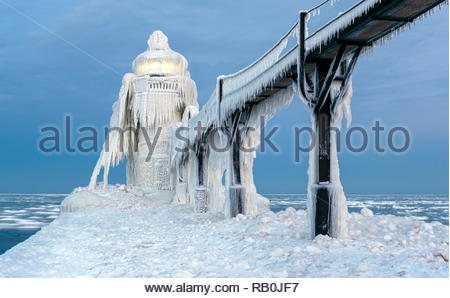 The St. Joseph, Michigan outer lighthouse on Lake Michigan covered in snow and ice and with the beacon brightly lit - Stock Photo