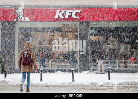 Belgrade, Serbia - December 15, 2018: Young person crossing snowy city street in snowfall towards KFC fast food restaurant, one man is shoveling snow - Stock Photo