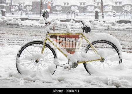 Belgrade, Serbia - December 15, 2018: One rental bike parked on the sidewalk in heavy snowfall - Stock Photo