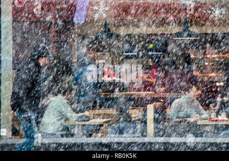 Belgrade, Serbia - December 15, 2018: Blurry man walking alone city street in heavy snowfall and people sitting in a restaurant window behind him - Stock Photo