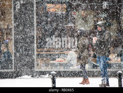 Belgrade, Serbia - December 15, 2018: Couple walking city street in heavy snowfall and people eating in a restaurant window behind them - Stock Photo