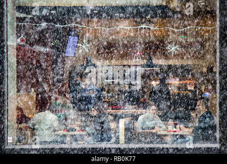 Belgrade, Serbia - December 15, 2018:People eating in a fast food restaurant on a snowy day, from outside through window glass - Stock Photo