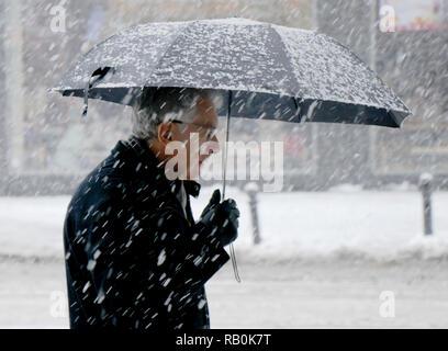Belgrade, Serbia - December 15, 2018: Elderly man walking alone under umbrella snowy city street in heavy snowfall - Stock Photo
