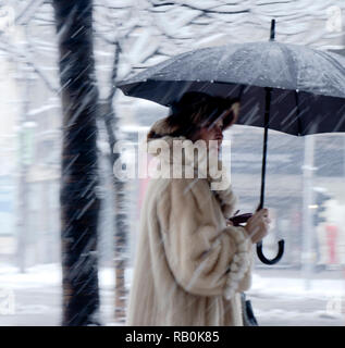 Belgrade, Serbia - December 15, 2018: Blurry stylish elderly woman walking alone under umbrella in heavy snowfall - Stock Photo