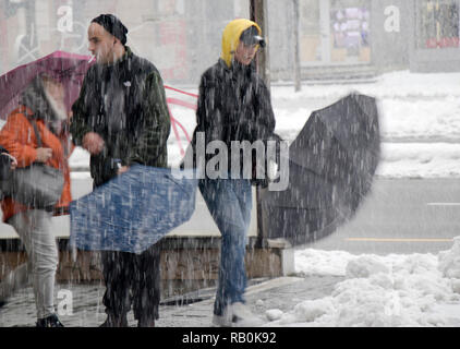 Belgrade, Serbia - December 15, 2018: Blurry people opening their umbrellas while walking out of subway passage to the snowy street - Stock Photo