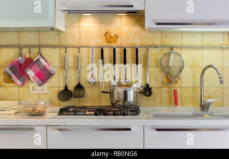 Front view of a modern white kitchen with a pot on the stove - Stock Photo