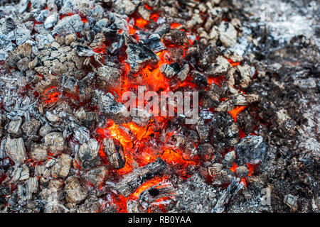 Background of actively smoldering embers and glowing coals of fire. - Stock Photo