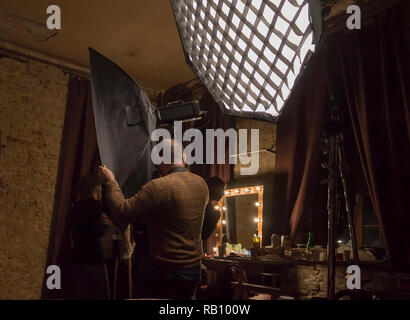 KIEV, UKRAINE, DEC 24, 2018: Working process of caucasian photographer in studio with lightboxes and mirror in frame. Unintended photography - Stock Photo