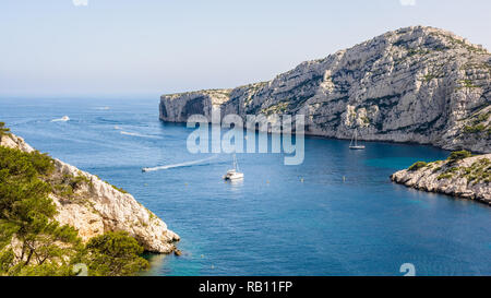 Panoramic view of the cap Morgiou on the mediterranean shore near Marseille, France, with motorboats cruising and sailboats mooring in the blue water. - Stock Photo