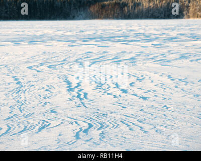 Wind formed patterns on snow blanket at a frozen lake in winter. - Stock Photo