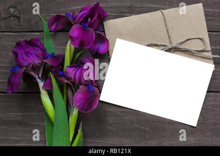 Blank white greeting card and envelope with purple iris flowers mockup on dark rustic wood background for creative work design. top view. flat lay - Stock Photo