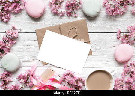blank greeting card or wedding invitation in frame made of pink cherry blossoming with coffee cup and macarons over white wooden table. mock up. flat  - Stock Photo