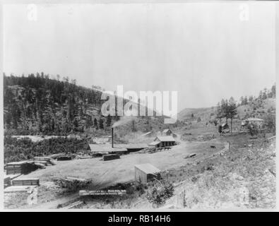 John C. H. Grabill,, photographer, Saw mill with smoke stack; piles of lumber; wooded hill in background..jpg - RB14H6 1RB14H6 - Stock Photo