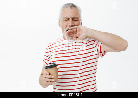 Waist-up shot of sleepy and tired grandfather with grey hair yawning with closed eyes holding paper cup of coffee standing sleepy with closed eyes in morning feeling tired waking up early - Stock Photo