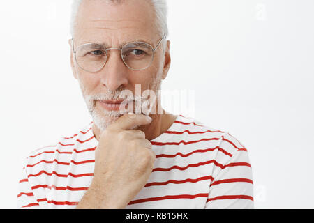 Man thinking how make family wealthy and happy. Portrait of intelligent smart and thoughtful good-looking mature retired businessman in grey hair and beard holding hand on chin gazing determined right - Stock Photo
