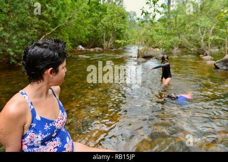 A mother watches her children swim in a stream, Alligator Creek, Townsville, Qld, Australia - Stock Photo
