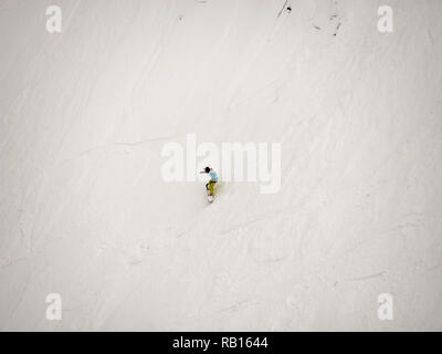 freerider snowboarder down the steep slope of white snow and trees in the mountains of the Caucasus. - Stock Photo