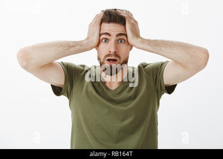 Close-up shot of frustrated nervous and hesitant cute clumsy boyfriend cannot slightly panicking holding hands on head in dismay and worry open mouth being unaware what do, troubled over white wall - Stock Photo