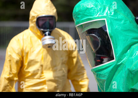 Two men in protective gear cleaning up after chemical accident or radiation accident. The inflatable gear to the right protects against contamination  - Stock Photo