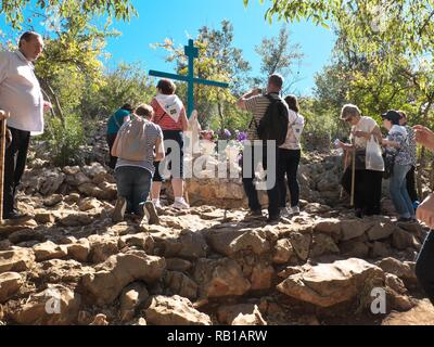 View of the Virgin Mary on Apparition Hill in Bosnia & Herzegovina  during a bright summer day showing lots of people praying - Stock Photo