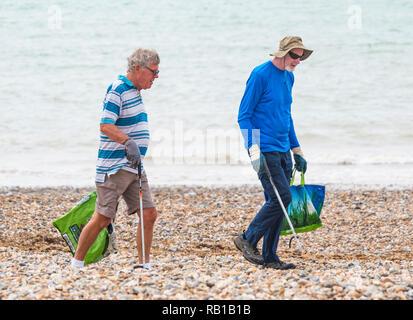 Pair of good samaritan volunteer men picking up litter from a beach in the UK. - Stock Photo