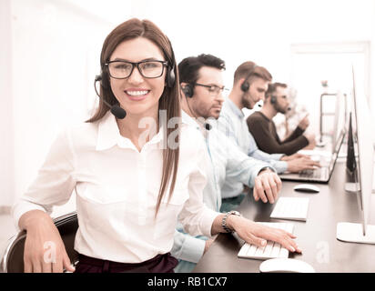 smiling call center employee works in a modern office - Stock Photo
