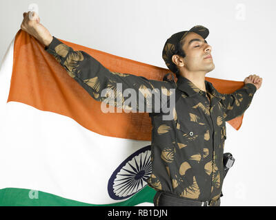 PORTRAIT OF INDIAN SOLDIER DRESSED IN UNIFORM HOLDING THE  INDIAN NATIONAL FLAG - Stock Photo
