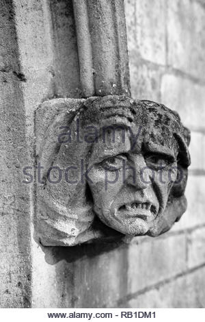 Ecclesiastical sculpture of a grotesque face caved in stone decorating the entrance to a church, Eaton Socon, UK. - Stock Photo