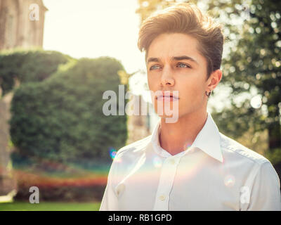 One handsome blue eyed young man in urban setting in European city park - Stock Photo