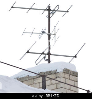 TV and communication aerials on snowy roof of residential house, multiple isolated dvb-t antennas winter scene, large detailed vertical closeup, rusty - Stock Photo