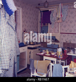 1970s, historical, a small cluttered kitchen, showing products scattered around it and a hanging clothes or washing line. - Stock Photo