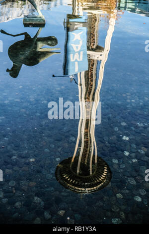 Space Needle and IMAX sign reflected in a pool at Seattle Science Center - Stock Photo