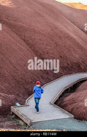 A lone female hiker on board walk at Painted Hills at John Day Fossil - Stock Photo