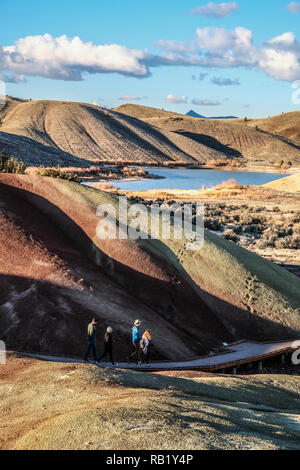 Hikers walk on board walk at Painted Hills at John Day Fossil - Stock Photo