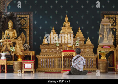 A side shrine at Lak Muang or the City Pillar Shrine, Bangkok, Thailand, where the city guardian spirits are worshipped, as well as, here, Buddha - Stock Photo