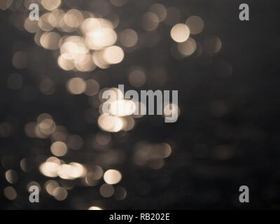Evening sun reflection in clear dark ice on pond. Decorative natural background.  Warm colors of evening sun in reflections. - Stock Photo