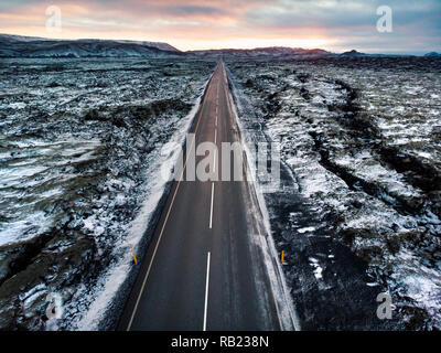 Road in Iceland surrounded by lava fields covered with snow aerial view - Stock Photo