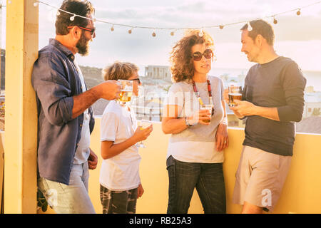 Group of people in friendship drink beer and orange juice together with mixed caucasian ages from child to adult having fun outdoor in terrace at home - Stock Photo