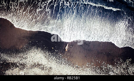 Young relaxed caucasian lady lay down at the beach on black vulcanic sand taking sun bath and waiting the big waves to dry her - vacation and travel t - Stock Photo