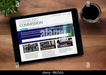 The website of Gambling Commission is seen on an iPad tablet, on a wooden table along with an espresso coffee and a house plant (Editorial use only). - Stock Photo