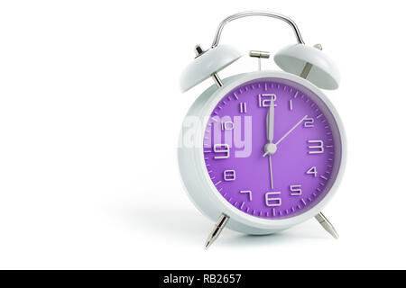 Twin bells analogue alarm clock with purple clock face shows 1 past 12, 12.01 AM PM; concept on white background - Stock Photo