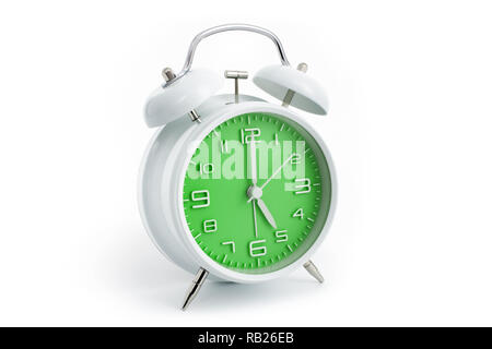 Twin bells analogue alarm clock with green clock face shows five hours, 5 AM PM; concept on white background - Stock Photo