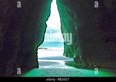 Daylight strikes wall highlighting green algal growth in view through archway rocks to dramatic sky and sea at Puponga South Island New Zealand. - Stock Photo