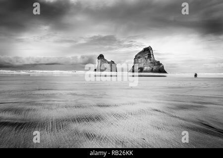 Two rocks and two walkers on Wharariki Beach on overcast day in moody atmospheric black and white image - Stock Photo