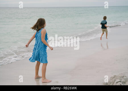 Cute Adorable Happy Young Little Girls in Pretty Dresses Playing On Vacation at the Tropical Beach by the Water on Destination Vacation - Stock Photo