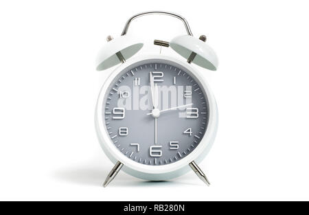 Table alarm clock shows time 1 minute to 12 o'clock with gray clock face, 11.59 AM PM, on white background - Stock Photo